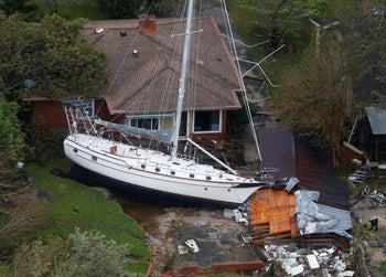 A sailboat is shoved up against a house and a collapsed garage Saturday, after heavy wind and rain from tropical storm Florence, September 15, 2018