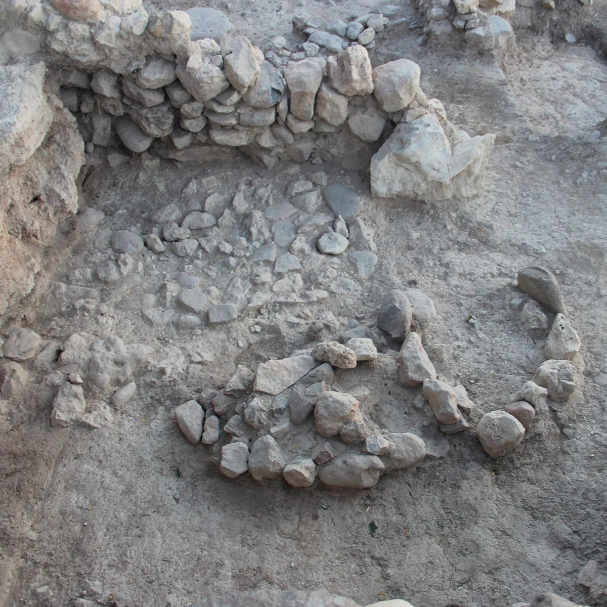 """Room in Iron Age I (11th century BCE) """"shrine"""" with semi-circle of stones facing a possible massebah (a worked standing stone)"""