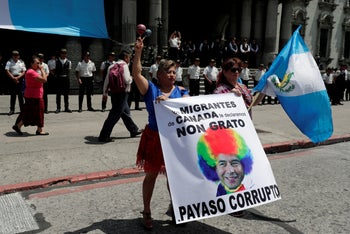 Women holding a banner showing Guatemalan President Jimmy Morales as a clown, during a protest to demand his resignation, Guatemala City, Guatemala, September 12, 2018.