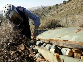 A researcher examines a cluster bomb that Israel fired on the southern village of Ouazaiyeh, Lebanon, November 9, 2006.