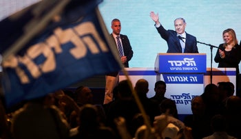 Israeli Prime Minister Benjamin Netanyahu greets supporters at the party's election headquarters In Tel Aviv, March 18, 2015.