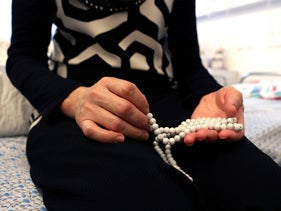 Ahmad's mother holding Islamic prayer beads on the bed where she sleeps next to her son in Ziv Medical Center, Safed, July 2018.