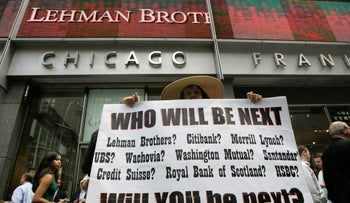 A protestor holds a sign in front of the Lehman Brothers headquarters Monday, Sept. 15, 2008 in New York.