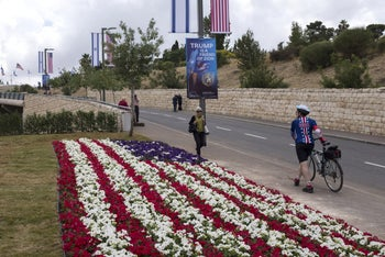 Visitors walk past a flower bed arranged in the colors of the 'Stars and Stripes' American flag on the road leading to the new U.S. embassy in Jerusalem, Israel. May 13, 2018