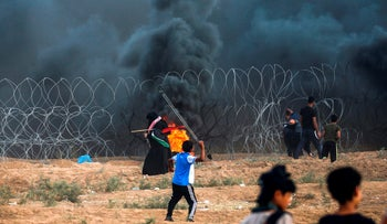 File photo: A young Palestinian protester uses a slingshot to hurl stones at Israeli forces during clashes following a demonstration at the Israel-Gaza border, on September 7, 2018