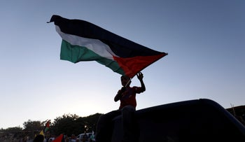 A boy holds a Palestinian flag during a protest against Israel's plan to demolish the Bedouin village of Khan al-Ahmar, in the occupied West Bank September 16, 2018