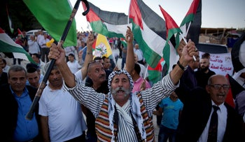 Palestinians protesters fly national flags and chant anti-Israel slogans in the West Bank village of Khan al-Ahmar , September 16, 2018.