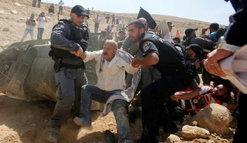 Israeli forces detain a Palestinian man as they protest against Israel's plan to demolish the Palestinian Bedouin village of Khan al-Ahmar, in the West Bank September 14, 2018.