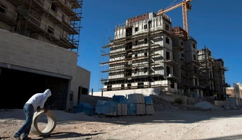 FILE Photo: A construction worker works at a site of a new housing unit in the east Jerusalem neighborhood of Har Homa.