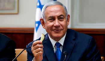Israeli Prime Minister Benjamin Netanyahu holds a piece of fruit as he attends the weekly cabinet meeting at the Prime Minister's office in Jerusalem September 5, 2018