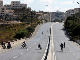 Children ride their bicycles in an empty street in Jerusalem during the Jewish holiday of Yom Kippur, September 19, 2018