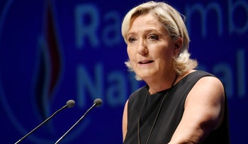 Leader of France's Rassemblement National (RN) far-right political party Marine Le Pen gestures as she delivers a speech at a meeting in southern France on September 16, 2018.