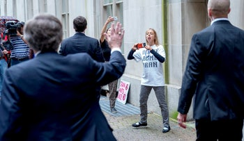 """CodePink co-founder Medea Benjamin, center right, wears a shirt that reads """"Don't Bomb Iran"""" and shouts at National security adviser John Bolton, left, as he departs the Mayflower Hotel after speaking at a Federalist Society luncheon, Monday, Sept. 10, 2018, in Washington."""