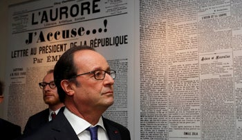 Former French President Francois Hollande stand in front of a reproduction of French writer's Emile Zola's (1840-1902) letter to the President of the Republic 'J'Accuse' in which he defended  Alfred Dreyfus, during a visit to the Zola house and Dreyfus museum in Medan, near Paris, October 2, 2016.