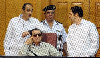 FILE PHOTO: Former Egyptian President Hosni Mubarak, and his two sons Gamal Mubarak, left, and Alaa Mubarak, right, attend a hearing in a courtroom at the Police Academy, Cairo, Egypt, September 2013