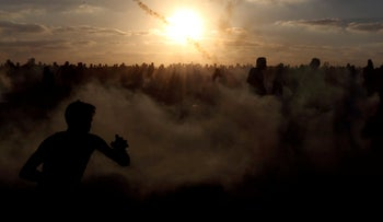 Palestinians run from tear gas during a protest at the Israel-Gaza border fence on September 21, 2018.