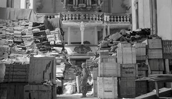 FILE Photo: An American soldier stands among German loot and records stored in a church at Elligen, Germany, April 24, 1945.