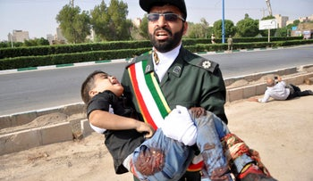 A Revolutionary Guard member carries a wounded boy after a shooting during a military parade, Ahvaz, Iran, September 22, 2018.