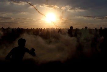 Palestinians run from tear gas during a protest at the Israel-Gaza border fence in the southern Gaza Strip, September 21, 2018.