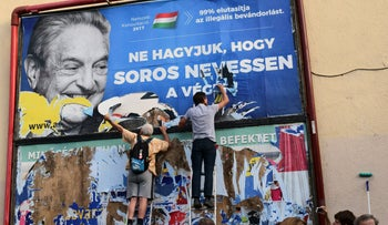 File photo: activists of the Egyutt (Together) party tear down an ad by the Hungarian government against George Soros, in Budapest, Hungary on July 12, 2017.