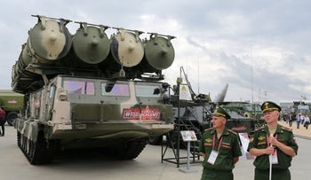 Military personnel stand beside a Russian S-300 long range surface-to-air missile system in Kubinka, Russia, on Aug. 21, 2018.