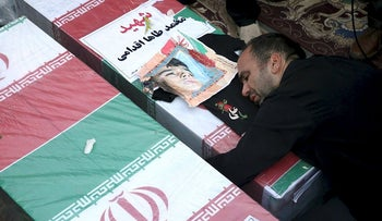Father of Mohammad Taha Eghadami, a 4-year-old boy who was killed in Saturday's terror attack on a military parade, mourns over his coffin during a mass funeral ceremony for the victims, in southwestern city of Ahvaz, Iran, Monday, Sept. 24, 2018