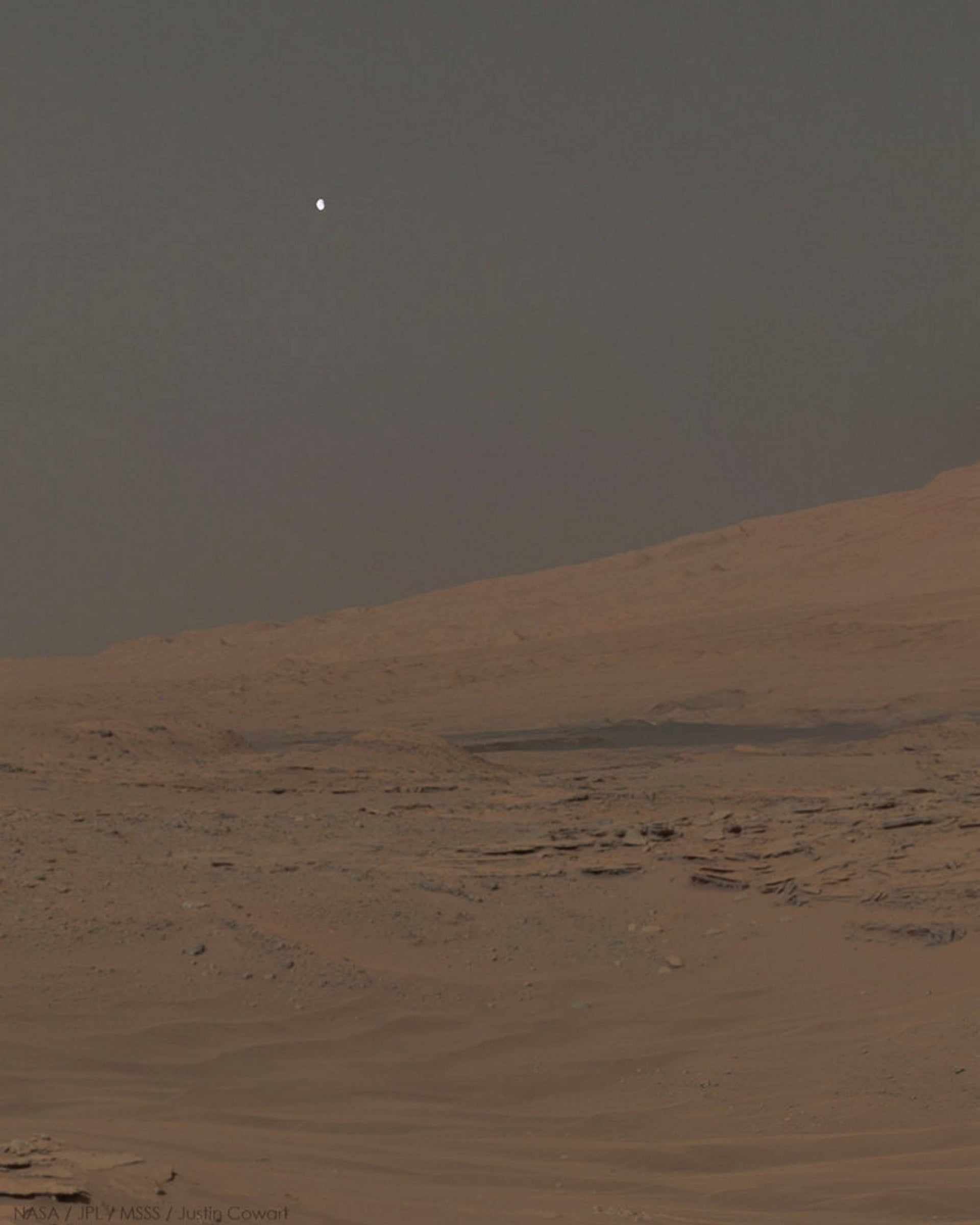 Phobos sets over Mt. Sharp, Mars, in a mosaic of three images captured by the Curiosity rover in 2014.