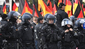 FILE PHOTO: Riot police stand by as people carry German flags during a march organised by the right-wing populist AfD in Rostock, north-eastern Germany on September 22, 2018