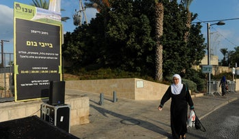 An Arab-Israeli woman crossing walking past a sign for festival activities in Acre, Israel, September 26, 2018