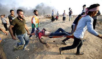 Demonstrators carry an injured Palestinian during clashes along the Israeli border fence, east of Gaza City, September 28, 2018.
