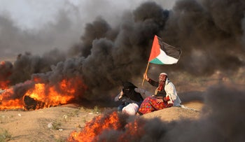 A Palestinian woman waving a national flag near burning tires during clashes along the border with Israel, September 28, 2018.
