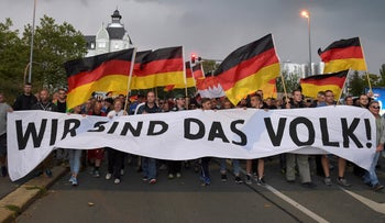 """FILE PHOTO: People attend a far-right """"Pro Chemnitz"""" group demonstration in Chemnitz, Germany, September 7, 2018. The banner reads: """"We are the people""""."""