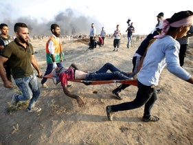 Demonstrators carry an injured Palestinian during clashes along the Israeli border fence, east of Gaza City on September 28, 2018.