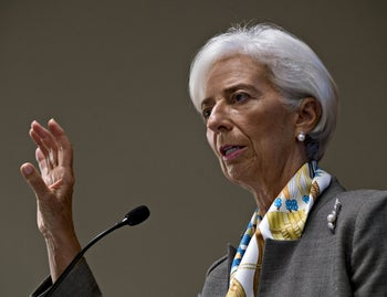 Christine Lagarde, managing director of the International Monetary Fund, speaks during a conference on sovereign debt in Washington, D.C., on Sept. 13, 2018: She said she isn't interested in securing a role as president of the European Central Bank or European Commission. She is wearing short white hair, pink lipstick, pearl earrings and brooch, and a grey jacket over a silk shirt.