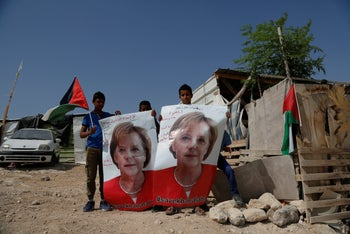 Bedouin children hold pictures of German Chancellor Angela Merkel ahead of her expected visit to Israel on Wednesday, in the West Bank Bedouin community of Khan al-Ahmar, Tuesday, October 2, 2018