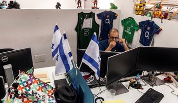 National flags of Israel sit on a desk partition as an employee speaks on a mobile phone at the Jerusalem Venture Partners JVP Media Labs in Jerusalem, Israel, on Wednesday, October 21 , 2015
