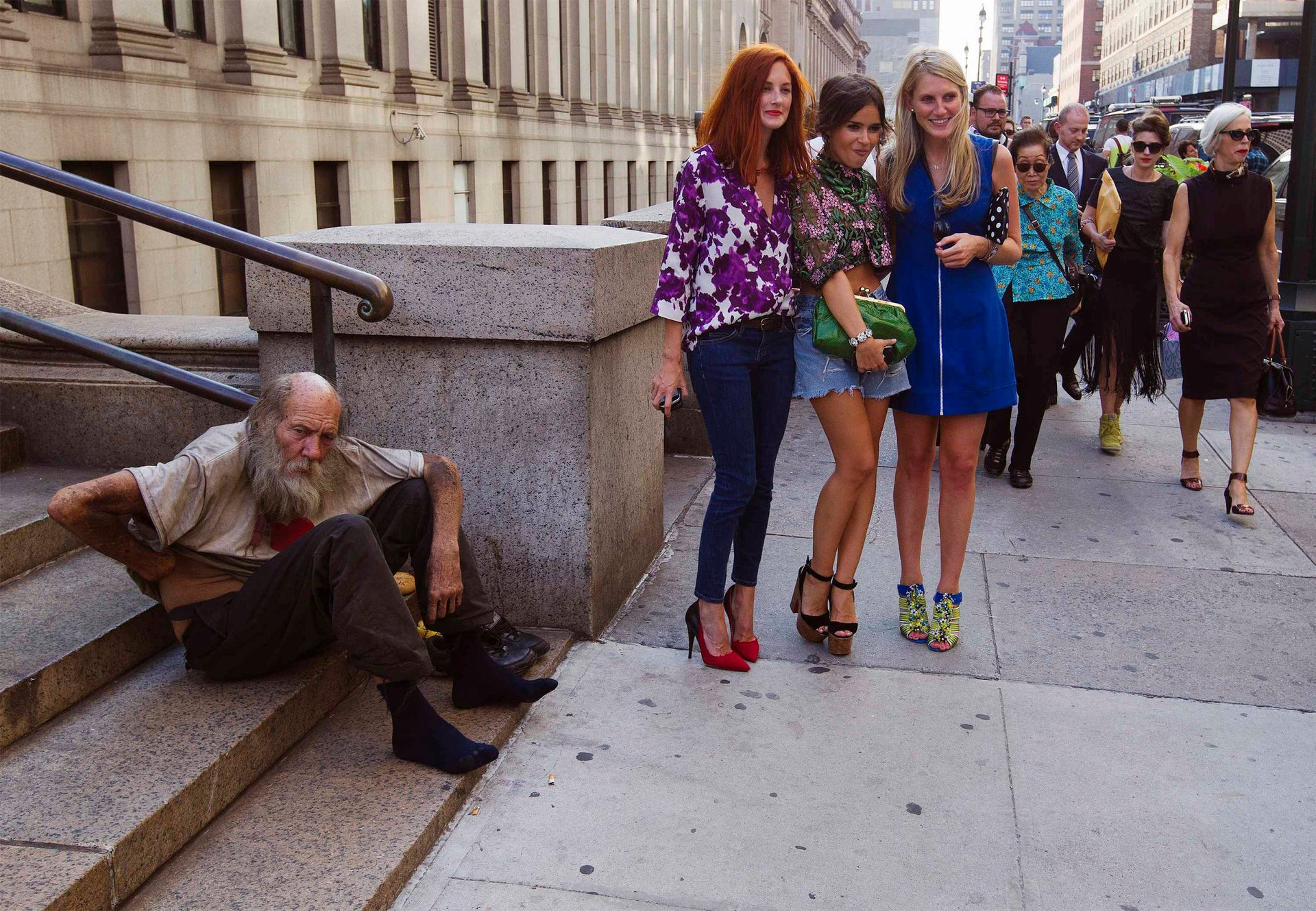 "Tourists in New York posing near a homeless man. ""In general, if you want to reduce suffering, mental health is a good place to start,"" says Kahneman."