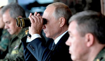Russian President Vladimir Putin looks through binoculars on a visit to a training ground, Eastern Siberia, Russia, September 13, 2018.