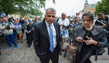 """Israeli politician Yair Lapid (C), party leader of Israeli Yesh Atid and former Israeli Finance Minister, is greeted by a man as he attends a """"Taking back Zionism"""" demonstration for Israel at the Raoul Wallenberg Square in Stockholm."""