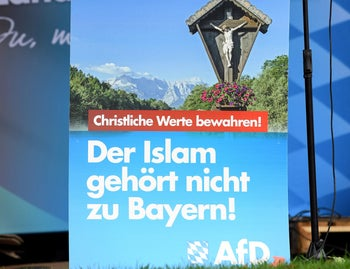 Germany's Alternative for Germany (AfD) co-leader Joerg Meuthen speaks in Abensberg, Germany, September 3, 2018. Illustrated with a crucifix, the poster in German reads 'To protect Christian values' and 'Islam does not belong in Bavaria.'