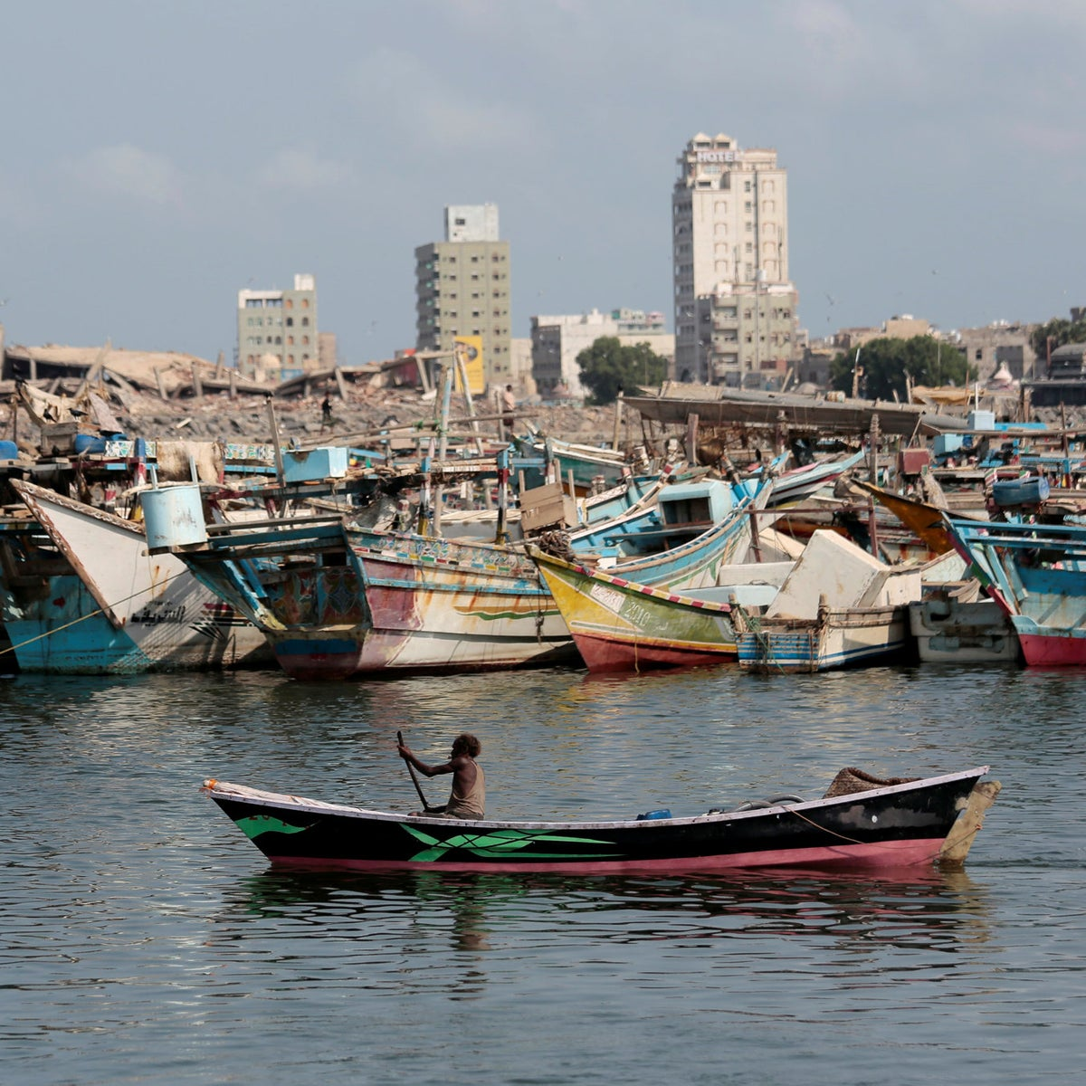 A fisherman paddles his boat past destroyed buildings on the coast of the port city of Hodeida, Yemen, Sept. 28, 2018.