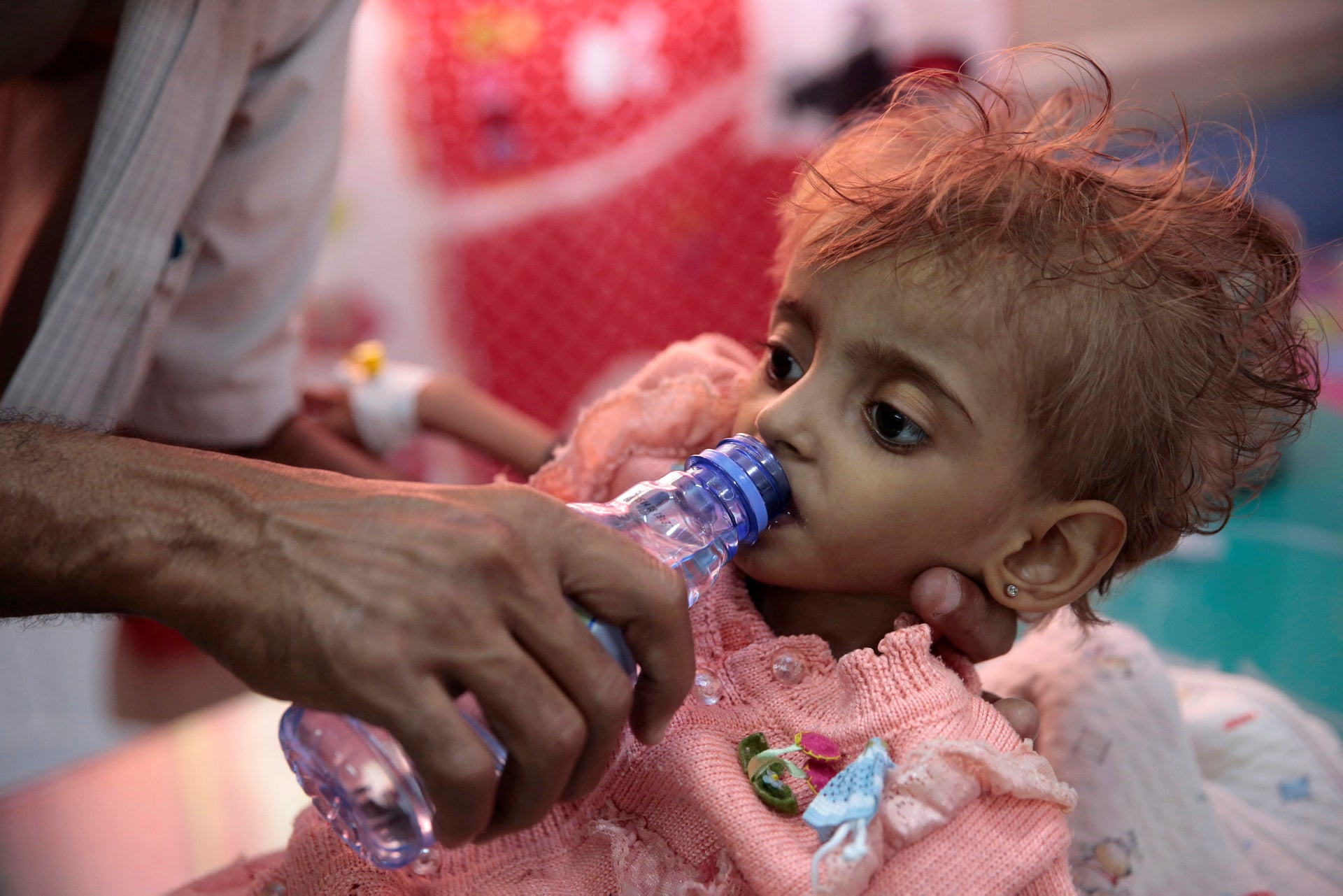 A father gives water to his malnourished daughter at a feeding center in a hospital in Hodeida, Yemen,  Sept. 27, 2018.