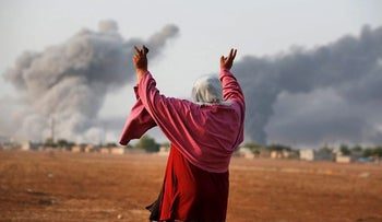 Syrian Kurd Kiymet Ergun, 56, gestures as she celebrates  in Mursitpinar on the outskirts of Suruc, at the Turkey-Syria border, as thick smoke rises following an airstrike by the US-led coalition in Kobani, Syria as fighting continued between Syrian Kurds and the militants of Islamic State group, Monday, Oct. 13, 2014