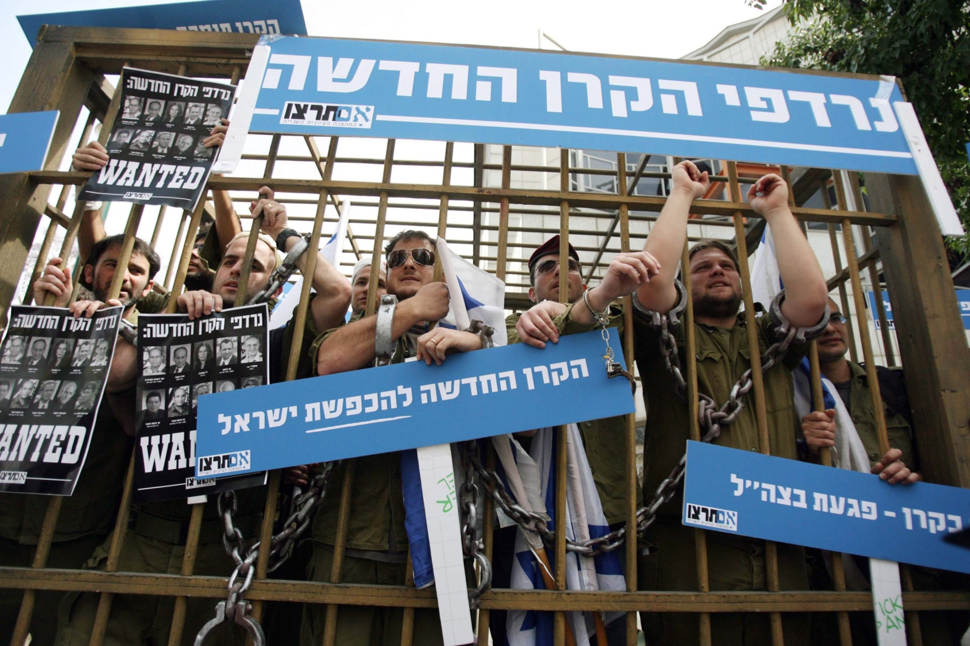 "An anti-NIF demonstration by lm Tirtzu. Signs read ""Persecuted by the New Fund"" and ""The New Israel-Slandering Fund."""