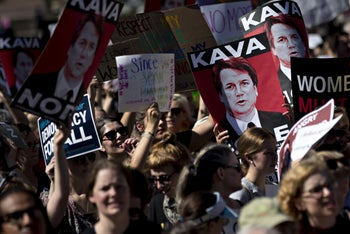 """Protesters opposed to Supreme Court nominee Brett Kavanaugh hold """"Kava Nope"""" signs while marching toward the U.S. Supreme Court in Washington, D.C., U.S., on Thursday, October 4, 2018"""