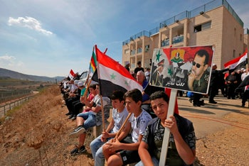 Members of the Druze community hold portraits of Syrian President Bashar Assad and Syrian national flags, October 6, 2018