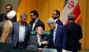 Iran's Parliament speaker Ali Larijani (C) is congratulated by MPs following the announcement of the results during a parliament session in Tehran.