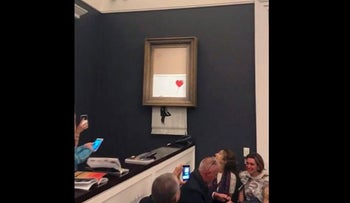 """In this grab taken from video on Friday, Oct. 5, 2018 people watch as the spray-painted canvas """"Girl with Balloon"""" by artist Banksy is shredded at Sotheby's, in London"""