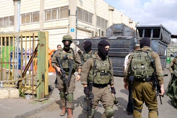 Israeli soldiers at the entrance to the West Bank factory where a shooting attack took place on October 7, 2018.