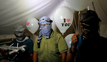 Masked Palestinian protesters hold incendiary devices attached to balloons to be flown toward Israel, near the Gaza-Israel border east of Rafah, on September 26, 2018